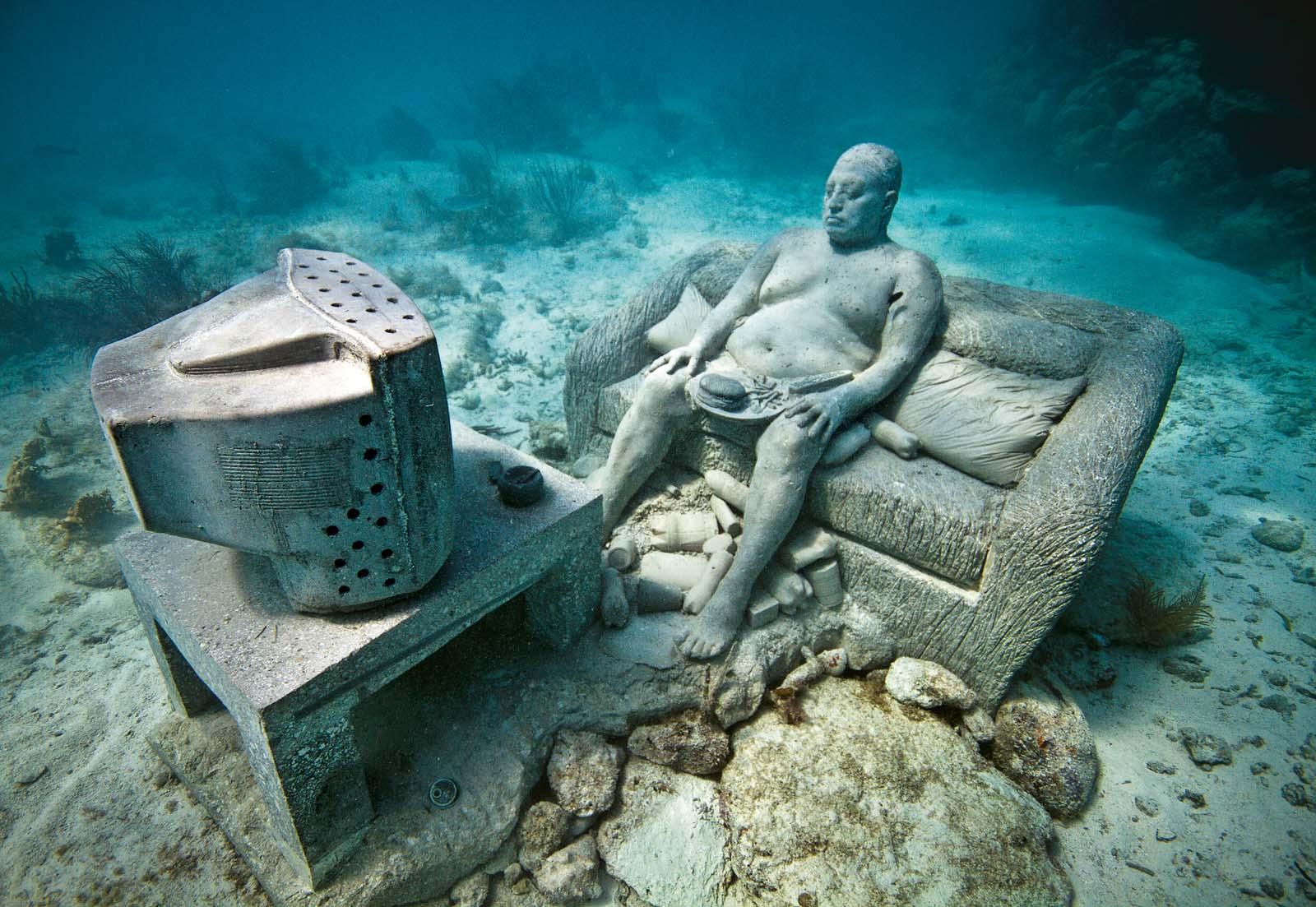 Подводный музей, Мексика. Фигура домохозяина на диване с гамургером перед телевизором.