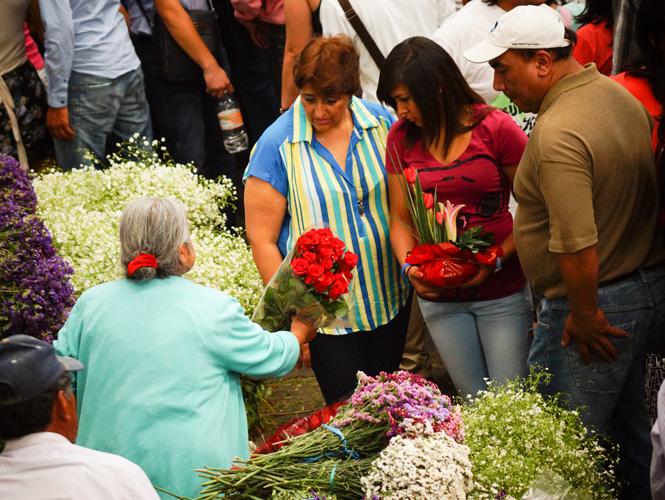 Продавцы помогают выбирать букеты цветов в День Матери в Мехико