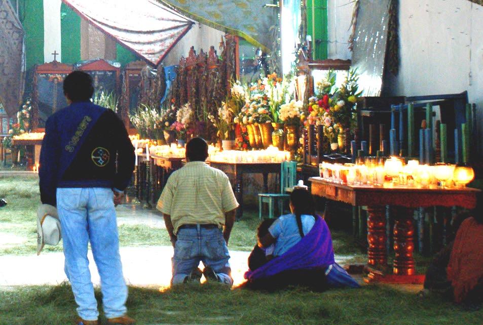 Хвойные ветки и множество свечей на полу Храма Сан Хуан, мество для молитв и преклонения. Деревня Сан Хуан Чамула, штат Чиапас